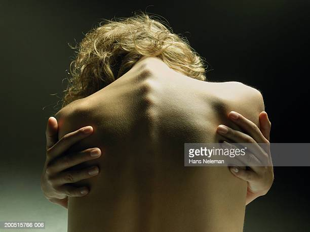 Naked young woman embracing self, close-up, rear view