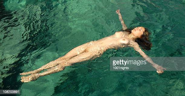 naked young woman floating on back in water - naturism stock photos and pictures