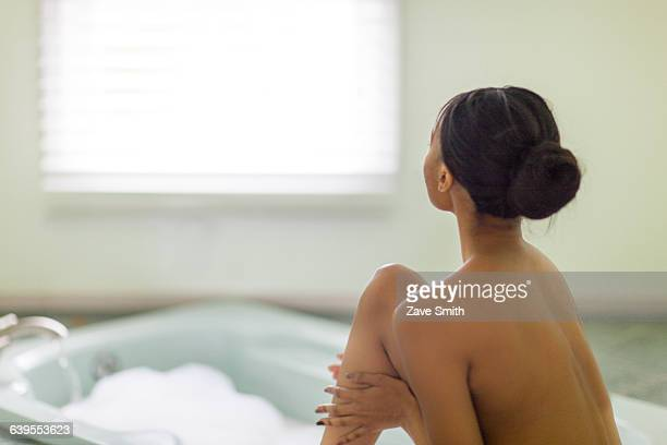 Naked young woman in bathroom gazing through window