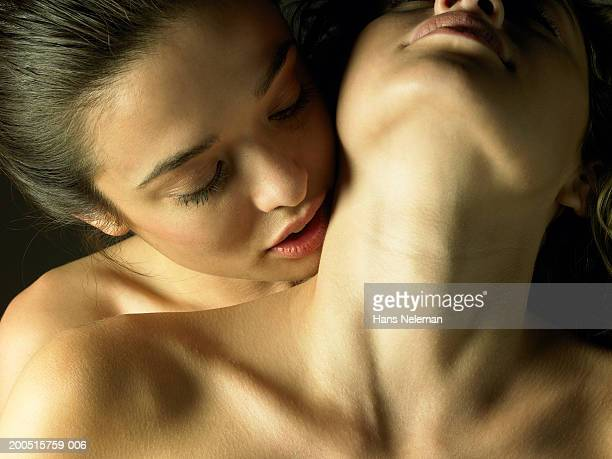 Naked young woman kissing woman on neck, close-up, front view