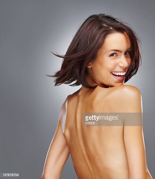 Naked young woman laughing against grey background