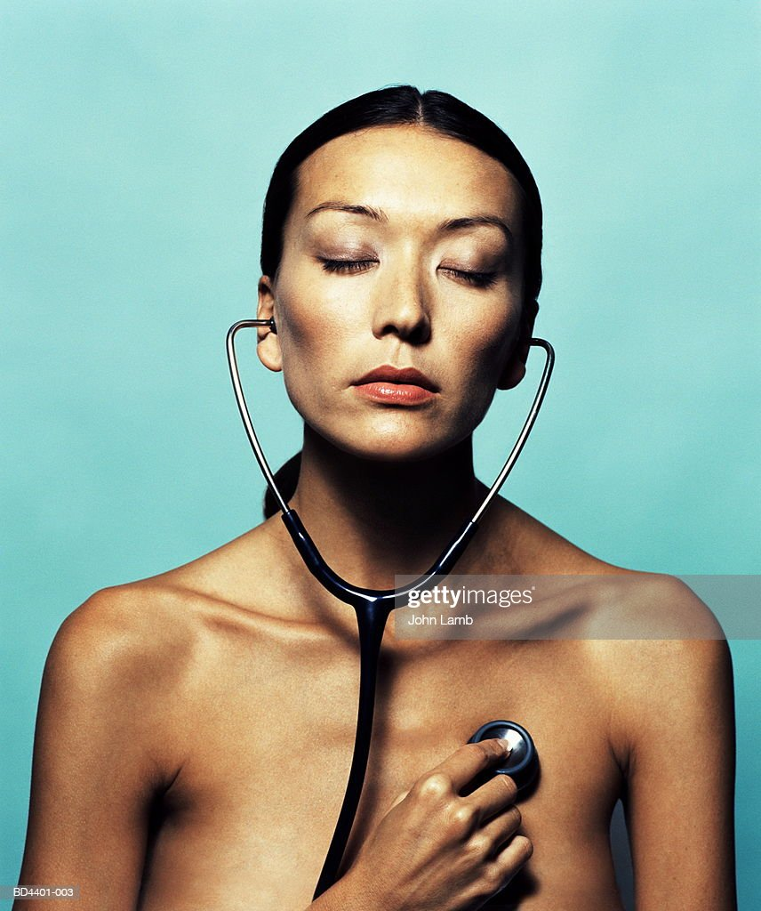 Naked young woman, listening with stethoscope, eyes closed : Foto de stock