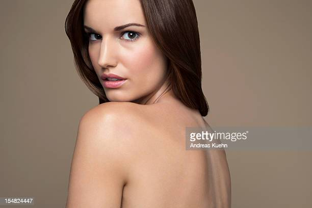 Naked young woman looking over shoulder, portrait.