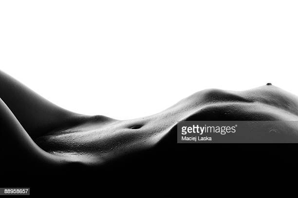 Naked young woman lying down, isolated on white