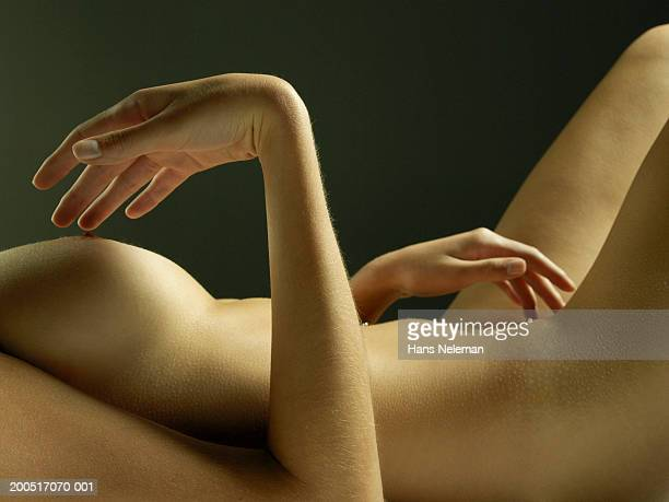 naked young woman lying on back, fingers touching nipple and groin - junge frau allein fotos stock-fotos und bilder