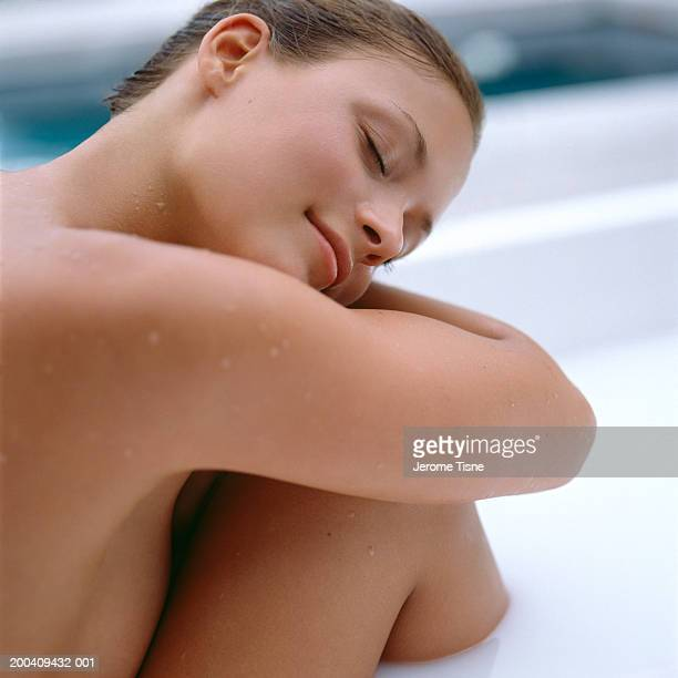 Naked young woman relaxing in milk bath