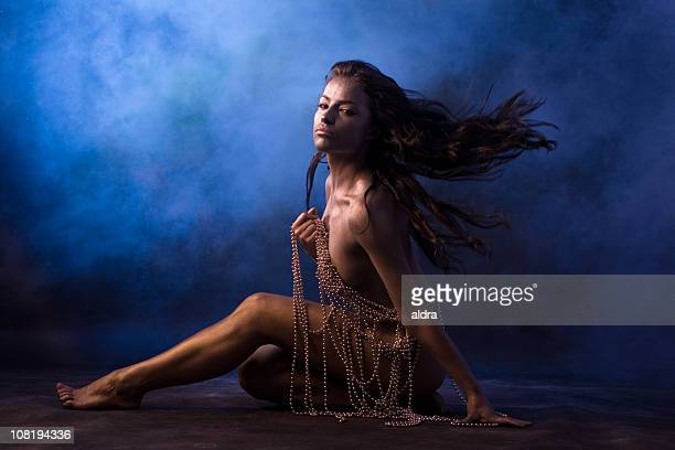 Naked Young Woman Sitting and Holding String of Beads