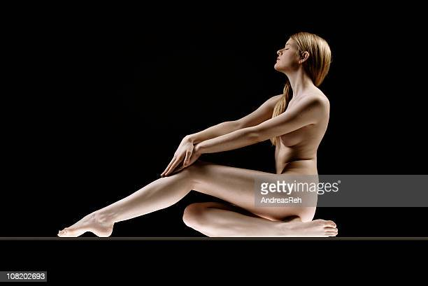 naked young woman sitting and posing on black background - german naturist stock pictures, royalty-free photos & images