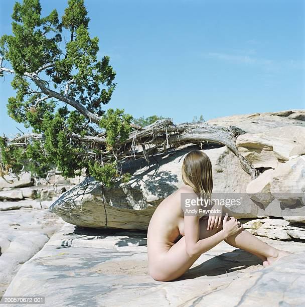 Naked young woman sitting atop rock in desert, looking away, side view