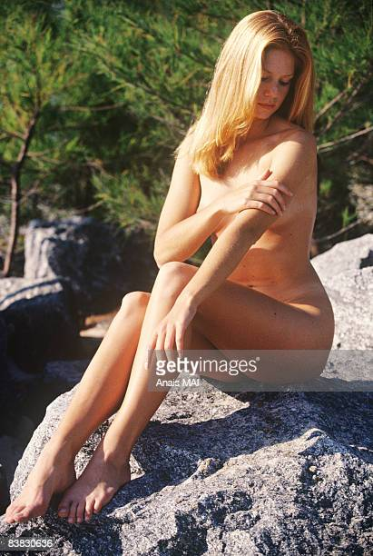 naked young woman sitting on a rock, outdoors - naturisme photos et images de collection