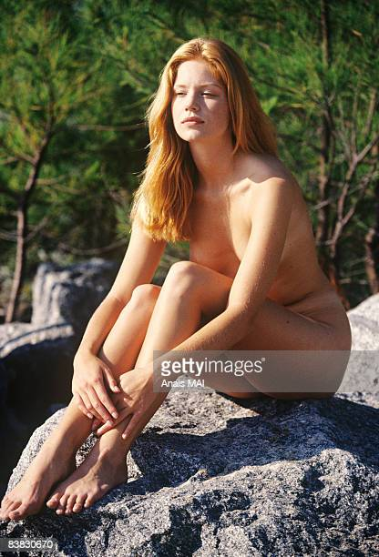 naked young woman sitting on a rock, outdoors - naturalist beach stock photos and pictures