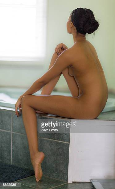 Naked young woman sitting on bath gazing through window