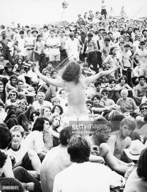 A naked young woman stands up amidst the crowd during the Woodstock Festival at White Lake Bethel New York August 1969