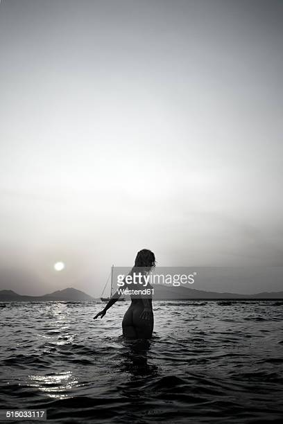 Naked young woman walking in the sea by twilight