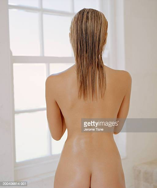 Naked young woman with wet hair, rear view