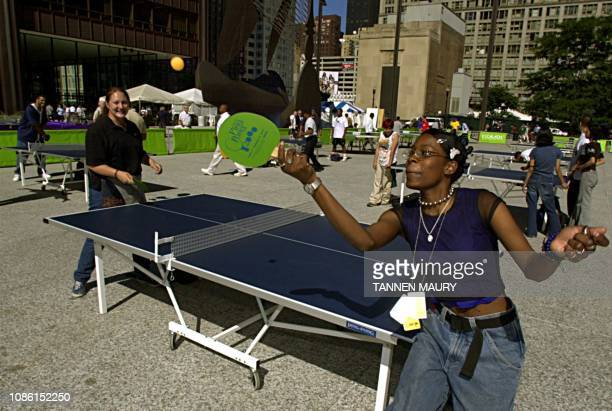 Nakema Williams makes a backhand return to playing partner Katie Guzik while playing pingpong in Chicago's Daley Plaza 04 August 2000 The city is...