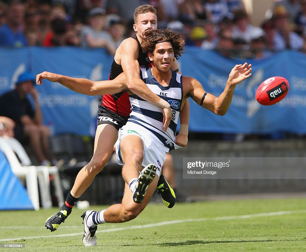 Nakia Cockatoo of the Cats kicks the ball away from Shaun Edwards of the Bombers during the 2016 AFL NAB Challenge match between the Essendon Bombers and the Geelong Cats at Deakin Resserve on March 5, 2016 in Shepparton, Australia.