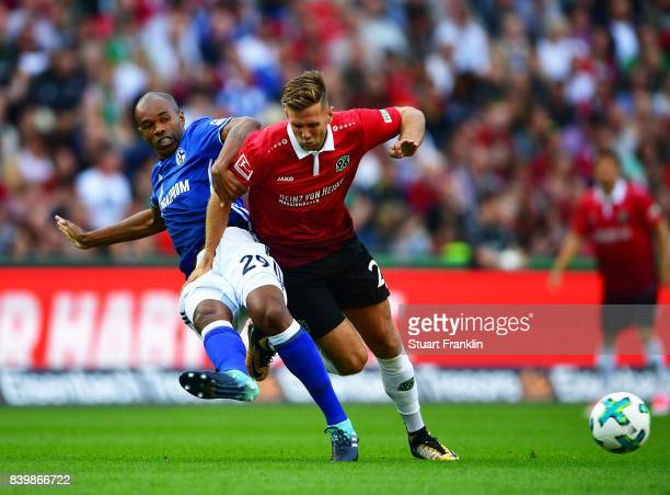 Naldo of Schalke 04 is challenged by Niclas Fuellkrug of Hannover 96 during the Bundesliga match between Hannover 96 and FC Schalke 04 at HDIArena on...