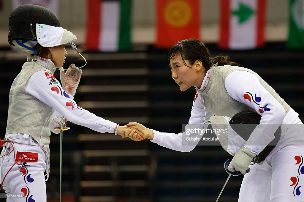Nam Hyun Hee of South Korea (L) and Jeon Hee Sook of South Korea shake hands at the end of their fight in the women's individual foil final during the 2015 Asian Fencing Championships at OCBC Arena on June 27, 2015 in Singapore.