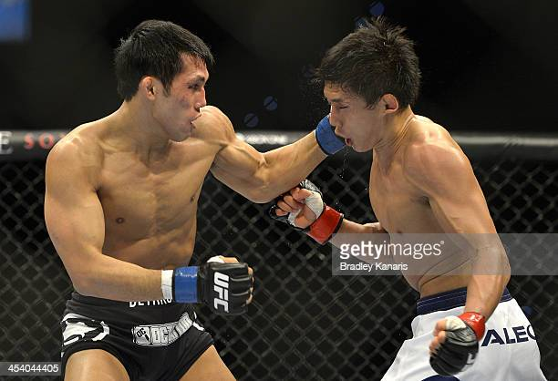 Nam Phan of the USA punches Takeya Mizugaki of Japan during their bantamweight fight during the UFC Fight Night event at the Brisbane Entertainment...