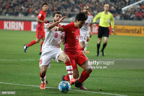 Nam TaeHee of South Korea competes for the ball with Almawas Mahmoud of Syria during the FIFA World Cup Qualification AFC Final Group Stage match...
