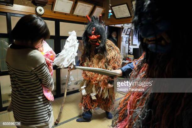 Namahage deities visiting a house during the Namahage festival of traditional folk event on New Year's Eve They shouting loudly to mother and child...