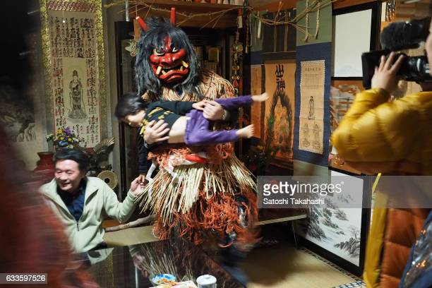 Namahage deity cradles a child in his arms during the Namahage festival of traditional folk event on New Year's Eve Namahage deities deliver an...