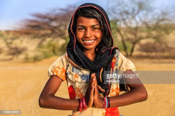 namaste! porträtt av lycklig indisk flicka i ökenby, indien - prayer pose greeting bildbanksfoton och bilder