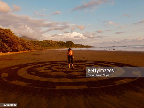 namaste. yoga.  sandart. uvita beach - naomi jarvis stock pictures, royalty-free photos & images
