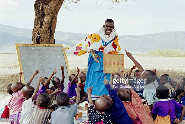 Namayiana Risanto teaching the pupils of Sanjan preschool under a tree in the Malambo district of Ngorongoro The region of Ngorongoro in Tanzania is...