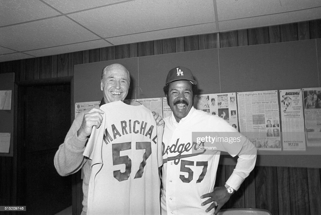 A name that used to bring a frown to the face of Dodger manager Walter Alson (l) now brings a smile. Los Angeles manager Alston holds up the shirt of newly acquired pitcher Juan Marichal (r) former pitching ace of the San Francisco Giants. The addition of Marichal should add more fuel to the already intense Dodger-Giant rivalry. Los Angeles has been looking for another starting pitcher and Marichal might just fill the spot.
