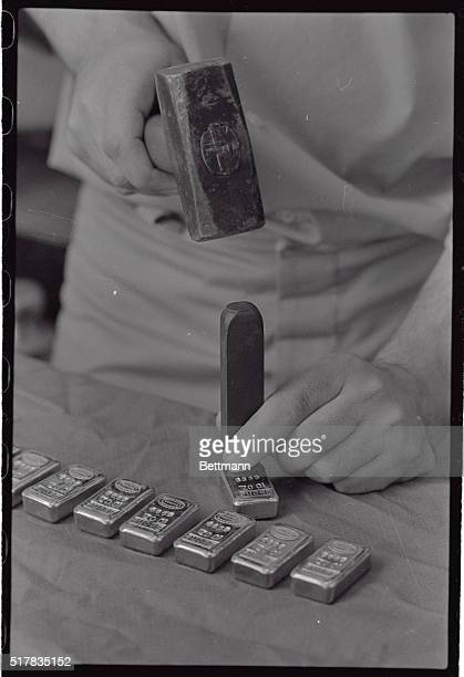 Name weight and lot number are stamped on 10ounce gold bars by hand at the Johnson Matthey Ltd plant at Brampton recently The Bache gold bar can be...