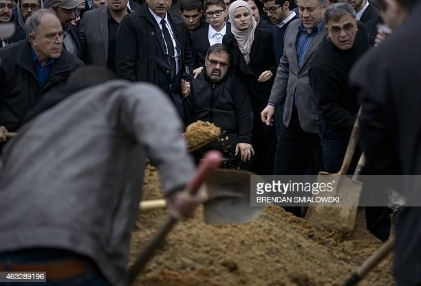 Namee Barakat watches with his daughter Suzanne Baraka as his son Deah Shaddy Barakat is buried February 12 2015 in Wendell North Carolina Community...