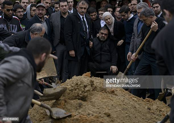 Namee Barakat watches with his daughter Suzanne Baraka as his son Deah Shaddy Barakat is buried February 12 2015 in Wendell North Carolina More than...