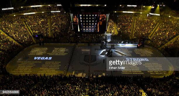 Names of the 58 victims of the October 1, 2017 mass shooting in Las Vegas are projected on the ice as the Vegas Golden Knights hang a banner in the...