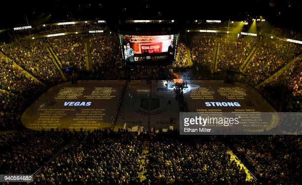 Names of the 58 victims of the October 1 2017 mass shooting in Las Vegas are projected on the ice as the Vegas Golden Knights hang a banner in the...