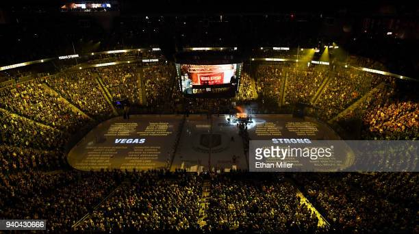 Names of the 58 victims of the October 1 mass shooting in Las Vegas are projected on the ice as the Vegas Golden Knights hang a banner in the rafters...