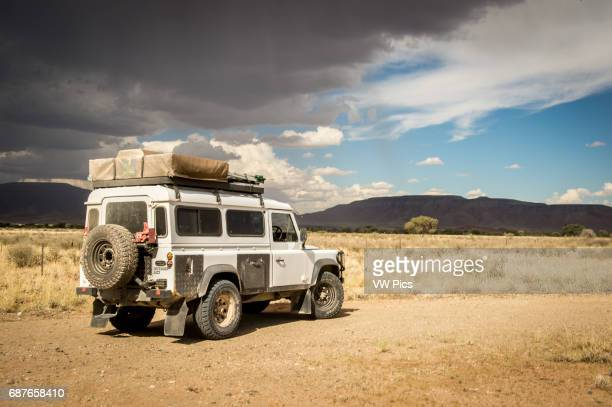 Namibia Africa Land Rover Defender 110 parked overlooking African landscape with dark clouds overhead