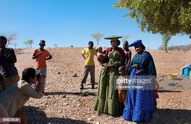 Namibia Africa Northern Desert tourists relating with colorful Herero tribe women in plaid dress and hat