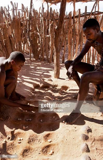 Namibia Africa remote Damara Tribe in Damaraland boys playing traditional game called llgus