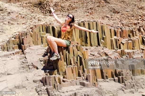Namibia, Damaraland, Twyfelfontein, Eoman sitting on basalt organ pipes