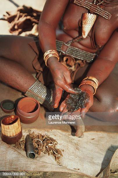 Namibia, Himba tribeswoman preparing a skin ointment, close-up