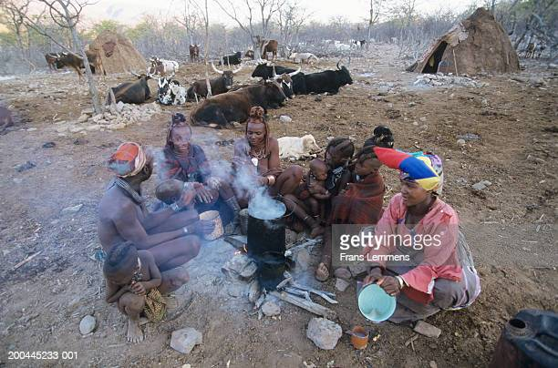 namibia, kaokoveld, near opuwo, family around fire, dusk,elevated view - mother and daughter smoking stock photos and pictures