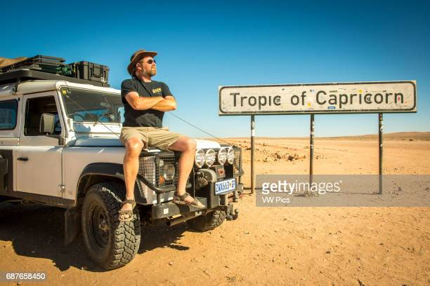 Namibia Man sitting on his Land Rover Defender 110 parked in the desert next to a sign for the Tropic of Capricorn