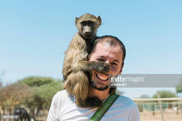 namibia, man with a baby baboon on his shoulder - monkey paw stock photos and pictures