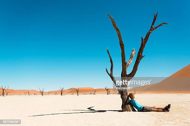 Namibia, Namib Desert, man resting at dead tree in Deadvlei