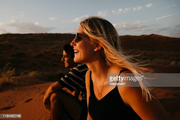 namibia, namib desert, namib-naukluft national park, sossusvlei, happy couple sitting on elim dune at sunset - extreme terrain stock pictures, royalty-free photos & images