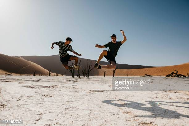 namibia, namib desert, namib-naukluft national park, sossusvlei, two men jumping in deadvlei - 25 29 jahre stock-fotos und bilder