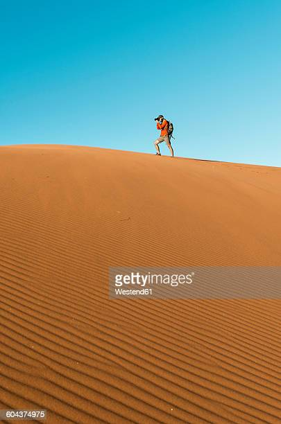 Namibia, Namib Desert, Sossusvlei, Man taking pictures on a dune