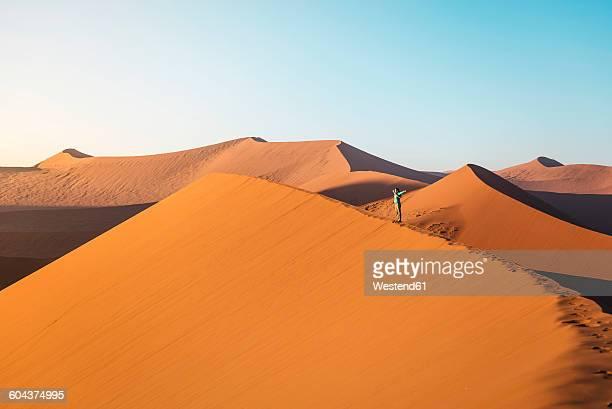 namibia, namib desert, sossusvlei. woman with raised arms on dune 45 at sunrise - ナミブ砂漠 ストックフォトと画像
